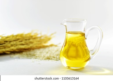 Rice bran oil in a glass jug with uncooked jasmine rice and ear of rice in the back on white background with copy space for text, selective focus
