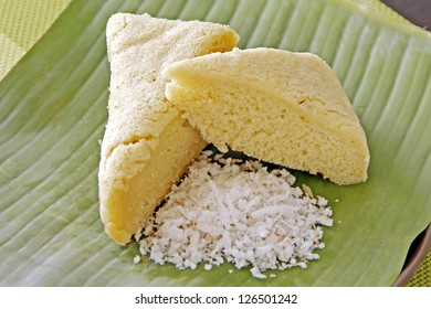 Rice cake with grated coconut fruit on banana leaf.