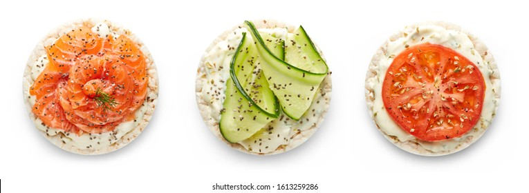 Rice cakes with cream cheese, fresh salmon, cucumber and tomato top view isolated on white background