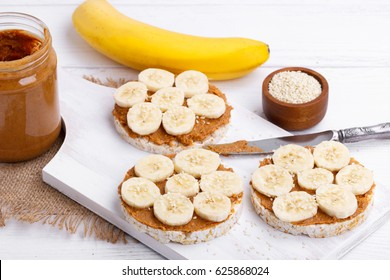 Rice cakes with peanut butter and slices of banana and sesame seeds on white wooden table