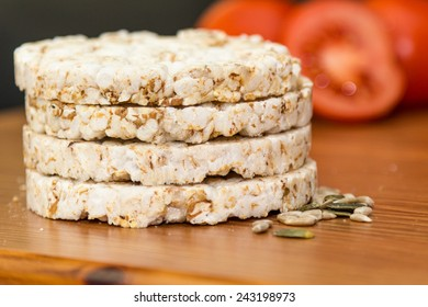 Rice cakes and seeds isolated with tomatoes in background