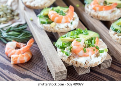 Rice cakes with sliced avocado cucumber shrimp and cream cheese.  Fresh parsley and rosemary. Vegetarian, vegan concept. Shallow depth of field. Coloring and processing photo