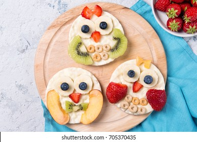 Rice cakes with yogurt and fresh fruits in a shapes of cute owls on a wooden board, food for kids idea, top view