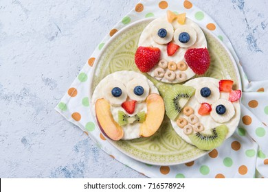 Rice cakes with yogurt and fresh fruits in a shape of cute owls on a plate, meal for kids idea, top view