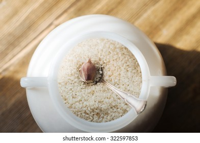 The rice in the can on brown background