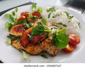 Rice with chicken breast on a white plate with parsley and tomatoes cherry