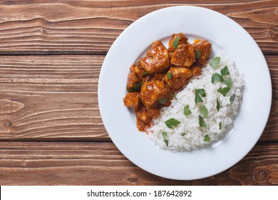 Rice with chicken in curry sauce and herbs on a plate with a horizontal top view.