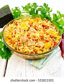 Rice with chicken, tomatoes, carrots, zucchini and garlic in a glass pan on a napkin, parsley on the background light wooden boards