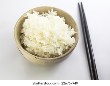 rice with chopsticks in a cup on white background