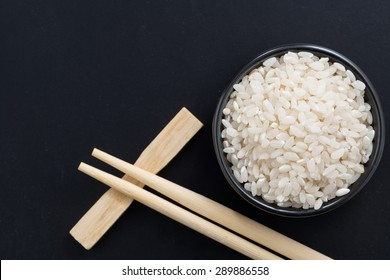 rice and chopsticks for sushi on a black background, top view, close-up