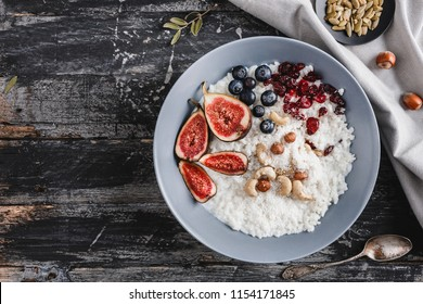 Rice coconut porridge with figs, berries, nuts, dried apricots and coconut milk in plate on rustic wooden background. Healthy breakfast ingredients. Clean eating, vegan food concept, close up