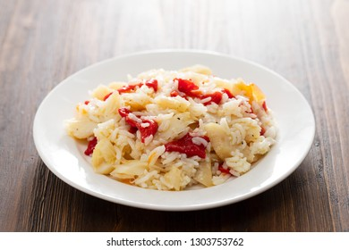rice with cod fish and red pepper on white plate