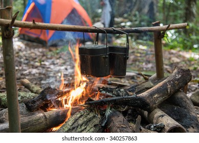 Rice cooking with army pot by using bonfire while camping in the forest.