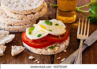 Rice cracker biscuits with tomato. mozzarella and basil. Perfect for weight loss diet.