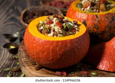 rice with dried fruit in a pumpkin on wooden table, closeup, horizontal