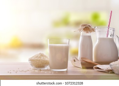 Rice drink in containers on a wooden table in a kitchen. Alternative milk. Front view. Horizontal composition
