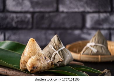 Rice dumpling, zongzi - Chinese rice dumpling zongzi on black brick background slate table, concept of Dragon Boat Festival traditional food, close up.