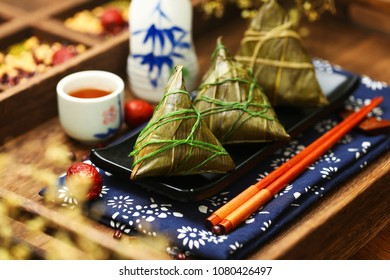 rice dumplings and wine on wooden plate