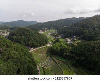 Rice fields in valley surrounded by forested mountains in rural Japan