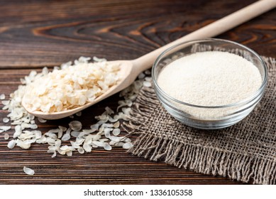 Rice flakes and flour on dark wooden background.