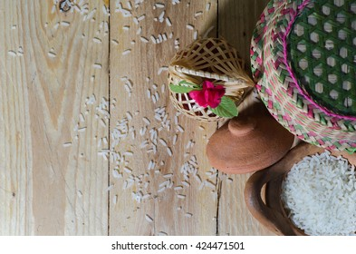 Rice grain in clay pot with wicker weave composition on wood background.