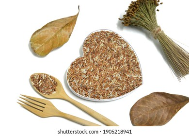 Rice grains in a plastic heart shape box surrounded by a bouquet of dry Xyrus indica, two dry leaves, a wooden spoon filled with rice grains and a wooden fork - Shutterstock ID 1905218941