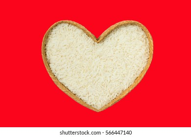 Rice with heart shaped isolated on red background.
