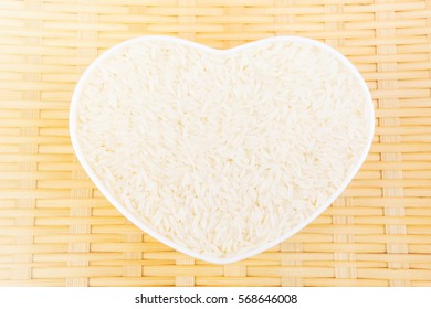 rice in a heart-shaped container on the bamboo tray, an idea of main food of Thai and Asia