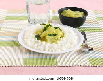 Rice and majjige huli or pumpkin or ash gourd sambar, a traditional and popular south indian vegetarian semi-liquid food. The rice-sambar combination is eaten by mixing the two items.