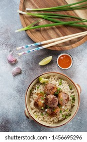 Rice with meatballs cooked in asian style, flatlay over light-grey stone background, vertical shot