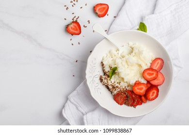 Rice milk porridge with strawberry and butter for breakfast. White background, top view, copy space.