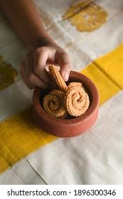 Rice Murukku or Chakli Indian deep fried snack for Pongal Onam in terracotta or clay pot on white Kerala sari background. popular in South India, Tamil Nadu, Andhra Pradesh and Sri Lanka