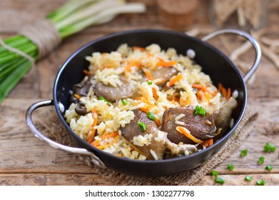 Rice with mushrooms in a pan on wooden background