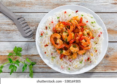 rice noodle and butter garlic fried shrimps sprinkled with pieces of chilli and chopped parsley on white dish on natural old wooden planks with spaghetti tongs, view from above
