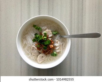 Rice noodle soup with vegetable and fried onion serving in white bowl, traditional Asian breakfast