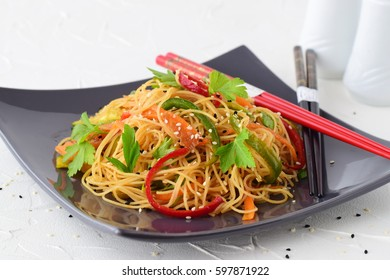 Rice noodles with carrot, broccoli and mushrooms in a black bowl on a black abstract background. Asian food. Healthy food