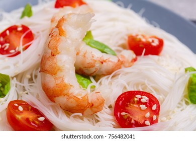Rice noodles with cherry tomatoes, royal shrimp and fresh greens. Indoors. Close-up.