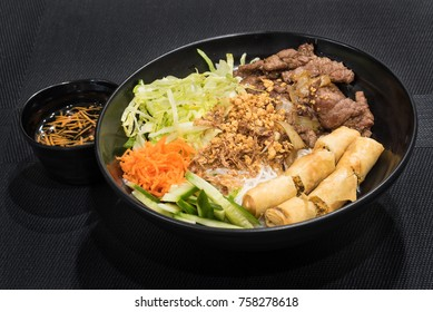 Rice noodles with grilled meat and spring roll, a popular Vietnamese cold rice vermicelli. Vietnamese cuisine.