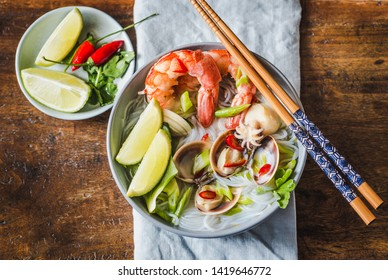 Rice noodles with shrimps and seafood, spicy asian style noodles in bowl.