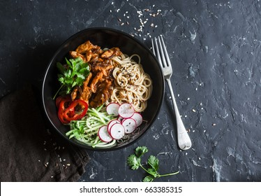 Rice noodles and teriyaki chicken stir fry with quick pickled cucumbers and radishes. On a dark background, top view. Asian food style