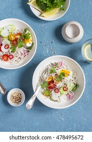 Rice noodles and vegetables salad. Healthy vegetarian food. On a blue background, top view