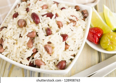 Rice and Peas - Caribbean coconut rice with red kidney beans, cowpeas and pigeon peas. Scotch bonnet chilies and lime on side. Close up.