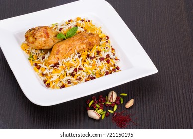 Rice Pilafs Known As Zereshk Polo a Persian Iranian Dish Topped With Saffron Rice Barberries And Pistachio Served With Flavoring Chicken Meat In Tomato Sauce On Wooden Table
