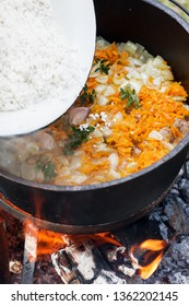 Rice pilau is cooking in the pot on the fire, asian dish on the fire. Camping in the nature and preparing food concept
