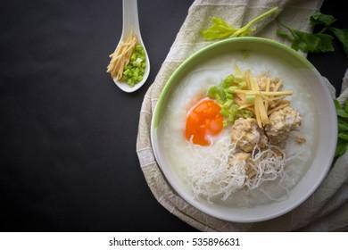 Rice porridge with boil pork and egg on black table,Thai food.