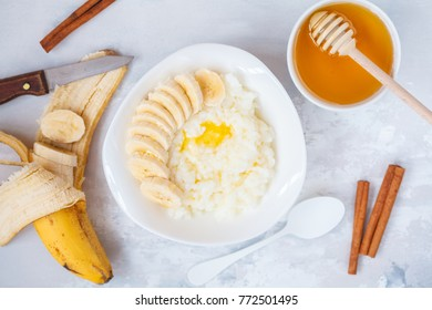 Rice porridge with butter, honey, banana and cinnamon. Top view, concrete background. Healthy breakfast porridge concept.