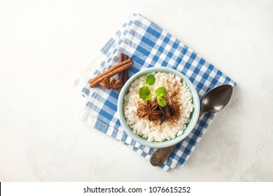 Rice porridge with cinnamon in a bowl on a light concrete background. Top view