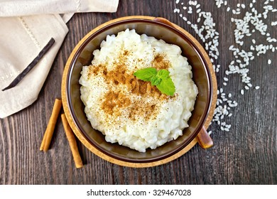 Rice porridge with cinnamon, mint in a brown bowl, napkin, spoon, vanilla pod on a wooden board top