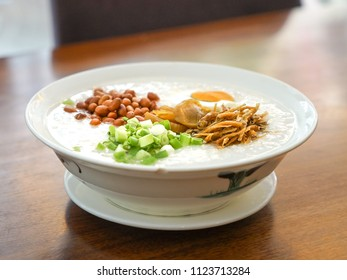 Rice porridge with peanuts, spring onion, vegetables and fried anchovies toppings