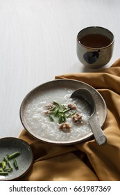 Rice porridge with pork put on white wooden table, rustic food.